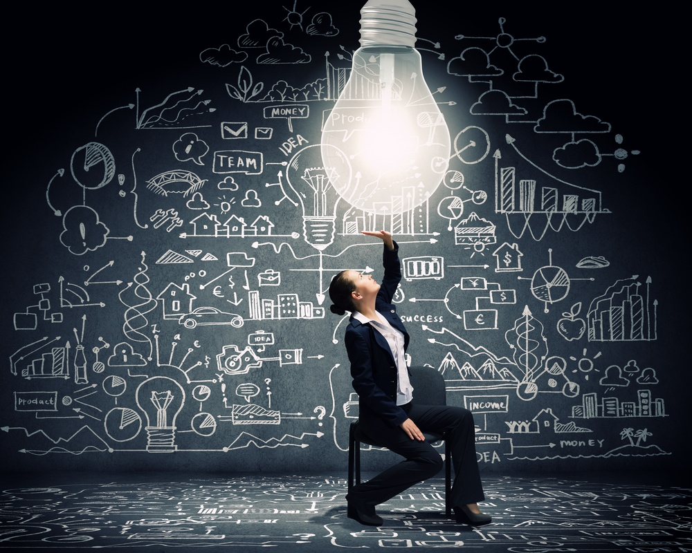 Young businesswoman sitting on chair with big light bulb above.jpeg