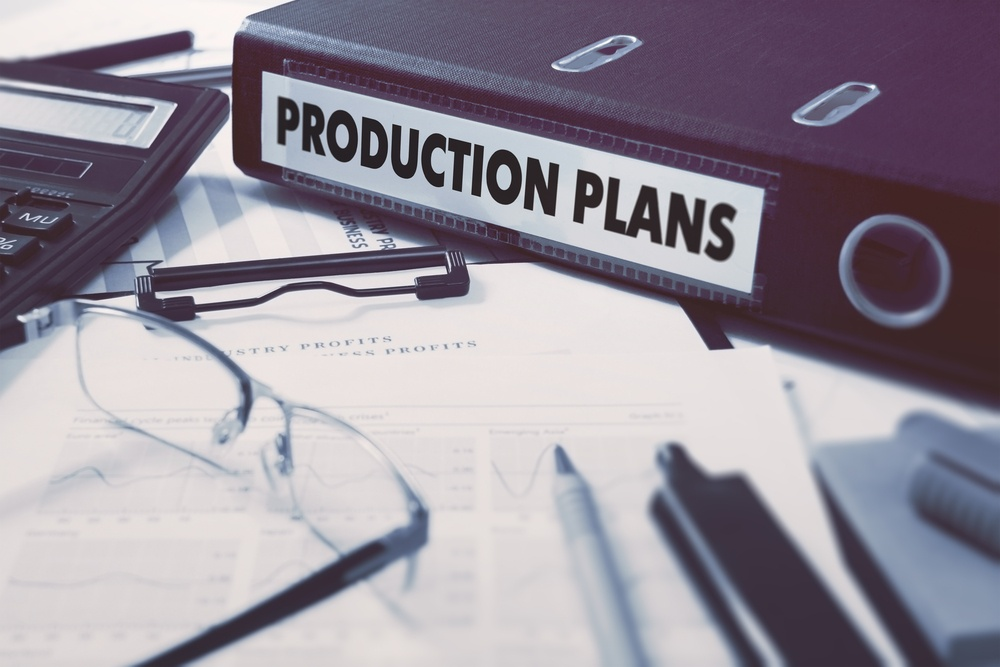 Production Plans - Office Folder on Background of Working Table with Stationery, Glasses, Reports. Business Concept on Blurred Background. Toned Image..jpeg